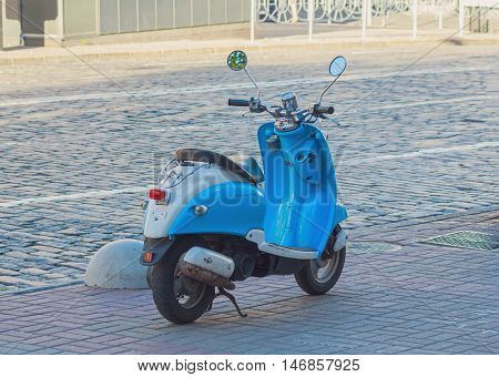 Blue scooter parked on the roadside. Transport