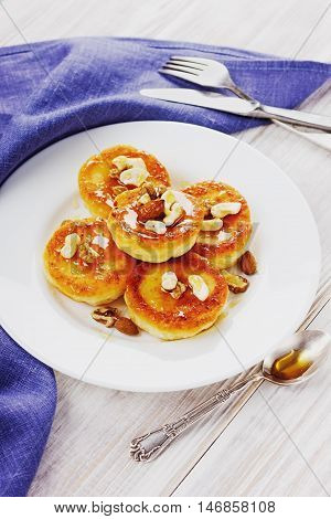 Fritters of cottage cheese with honey and nuts on a white plate.