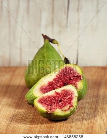 ripening figs   on wooden background,   one fruit -  cutting,  visible the pulp with seeds