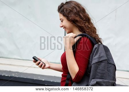 Female Backpacker Reading Text Message On Her Mobile Phone