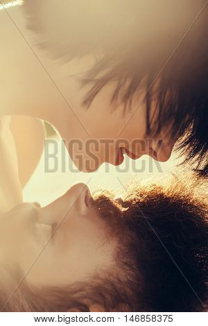 Young woman with short brunette hair pretends to kiss man handsome hipster with beard moustache sensual couple in sunlight on nature