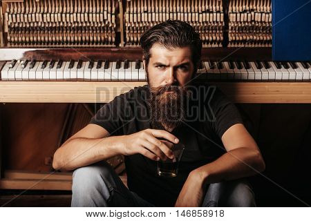 Bearded Man With Glass Near Wood Piano