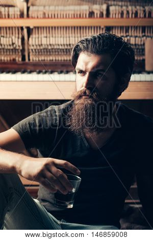 handsome bearded man with stylish hair mustache and beard on serious face drinking brandy or whiskey from glass near old wooden open piano with keyboard as musician