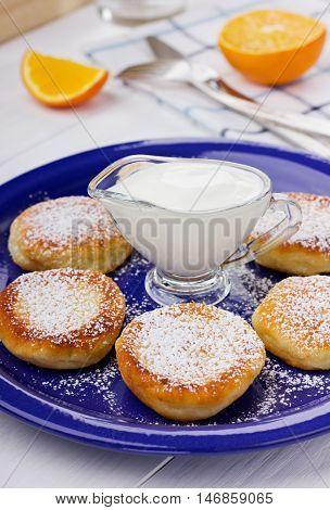 Fritters of cottage cheese with sour cream on a white background.