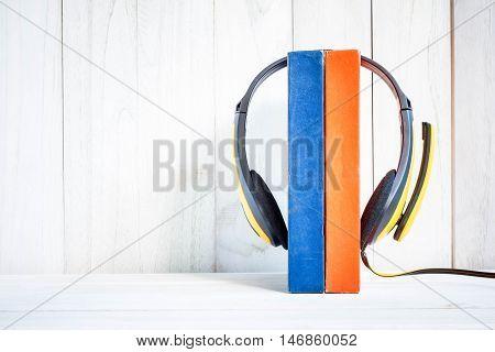 Headphones on books on white wood background