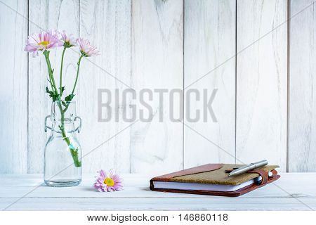 notebook and pen with flower on white wooden table