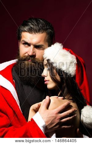 sexy young couple of pretty woman topless in santa claus hat and handsome bearded man with long beard in christmas or new year red coat embracing on purple background