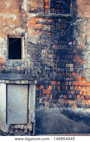 Ruins of old destroyed red brick house with burnt grunge walls empty windows and rusty door on masonry background