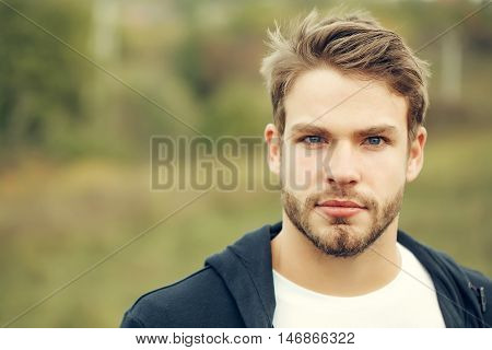 Young guy with bearded handsome sexy serious face blue eyes brown hair in dark hoody posing outdoor on natural background