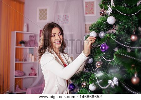 Young happy woman decorates a Christmas tree. The concept of the New Year and Merry Christmas