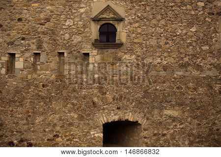 Small ornate window on old medieval stone fortress facade wall outdoors sepia-toned on masonry background