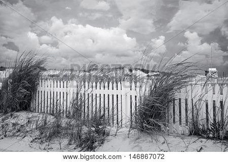 A white picket fence along the sand dunes in Seaside Park New Jersey.