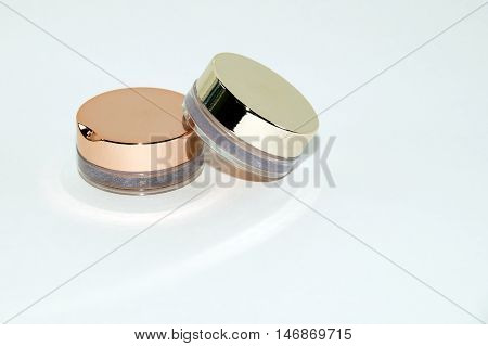 Two eyeshadow glass boxes on white background with soft shadows and reflections .
