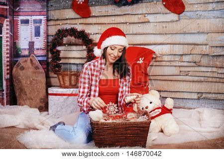 Beautiful happy girl in red shirt and Christmas hat. The concept of the New Year and Merry Christmas