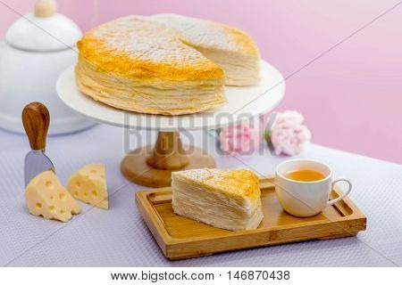 Cheese cake, sliced, with tea and cheese, selective focus