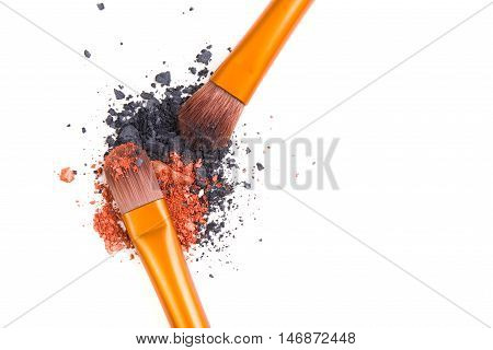 Professional makeup brushes set and loose powder eyeshadows isolated on white background, visage and cosmetic tools macro shot