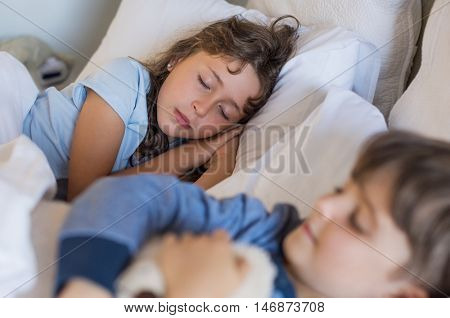 Little children sleeping together on bed. Cute little girl dreaming in her sleep. Children sleeping after having a tired day.