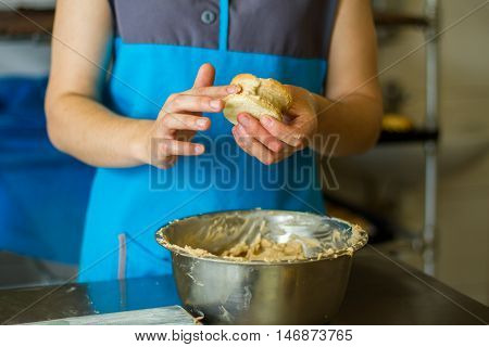 Woman's hands with cookie sandwich. Biscuits and bowl with custard. Employee of pastry cafe. Working hours in the kitchen.