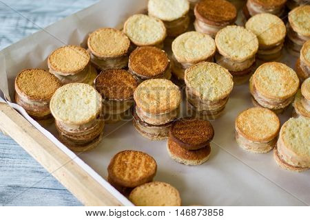 Yellow cookie sandwiches. Wooden tray with sweets. Crispy biscuits with vanilla custard. Cook delicious pastry at home.