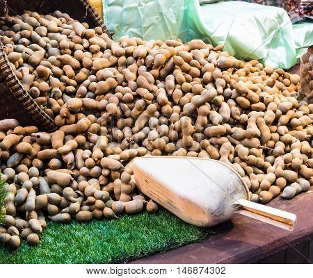 Stacked tamarind fruits for sale in market.