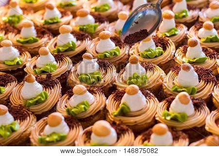Rows of decorated desserts. Spoon with chocolate crumbs. Adding the last ingredient. Soft dough and whipped cream.