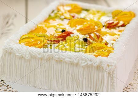 Colorful decorated cake. Pieces of fruits and jelly. Dessert with butter cream. Custom made cake in restaurant.