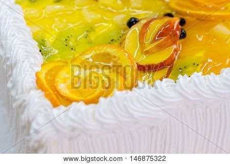 Cream and slices of fruit. Apple and kiwi in jelly. Freshly cooked cake. High content of calories.