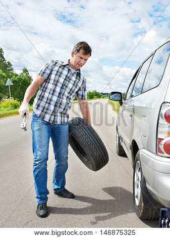 Man Changing A Spare Tire Of Car