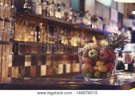 Blurred back bar. Bottles of spirits and liquor at the bar. Blurred desk in bar.
