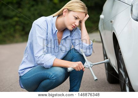 Frustrated Female Driver With Tire Iron Trying To Change Wheel
