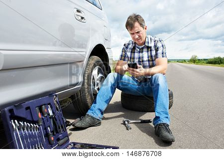 Man With Phone Is Calling In Service Of Spare Tire Car