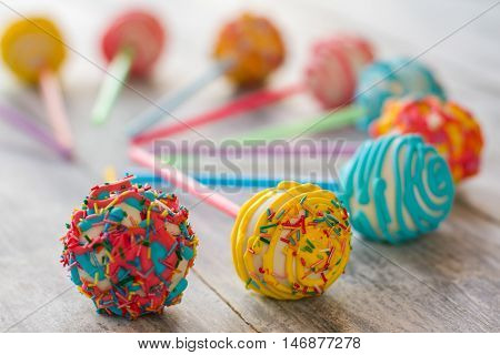 Sweets with bright glaze. Candies on gray wooden surface. Cake pops from pastry shop. Make small party for kids.