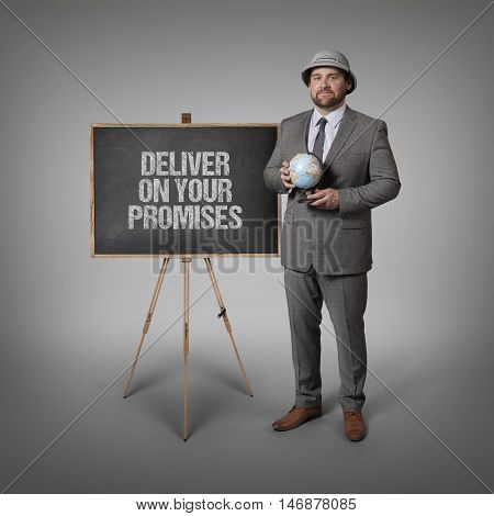 Deliver on your promises text on blackboard with businessman holding globe in hands