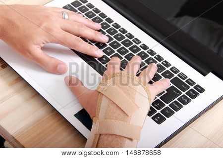 man with carpal tunnel syndrome using computer
