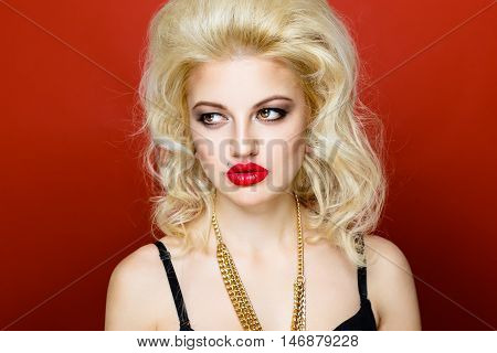 Close up portrait of beautiful blonde glam rocker woman with red lips on red background