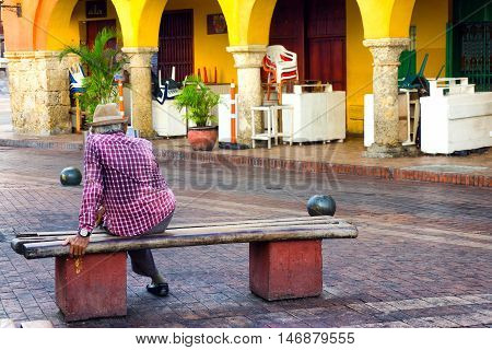 CARTAGENA COLOMBIA - MAY 25: Elderly man sitting on a bench in the historic center of Cartagena Colombia on May 25 2016