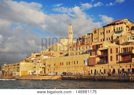 TEL AVIV, ISRAEL - NOVEMBER 22, 2014: Sunny day. The ancient port of Old Jaffa, Tel - Aviv. People walk on the promenade on warm day