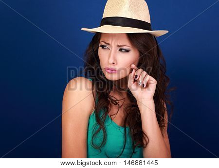 Annoyed Suspicious Woman In Straw Hat Lookig With Hand Near Face On Blue Background