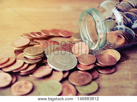 Save money concept Old coins spilling out of a glass bottle, Money for income and expenditure vintage style, Save money for prepare in the future