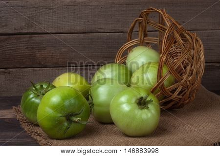 unripe green tomatoes in a wicker basket on a wooden background and sackcloth.