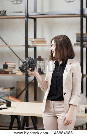 Laughing woman standing with camera at office. Beautiful female photographer looking at funny photo and smiling at her work