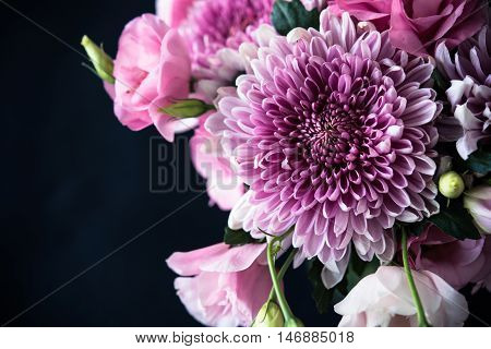 Bouquet of pink flowers closeup on black background, eustoma and chrysanthemum, elegant vintage floral decor