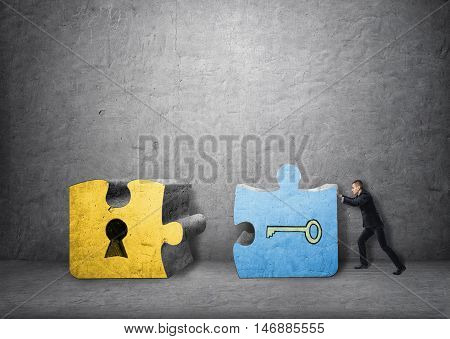 Businessman pulling together a key and a keyhole pieces of jigsaw puzzle. Solving problems. Deliberating and analyzing. Solution and answer.