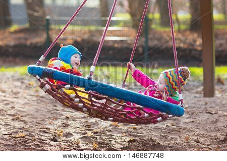 Little boy and girl on a playground. Child playing outdoors in autumn. Kids play on school yard. Happy kid in kindergarten or preschool. Children having fun on cold fall day. Toddler on a swing.
