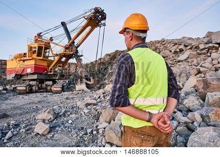 Worker looks on excavator works at opencast