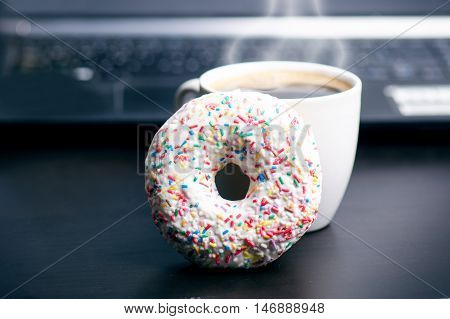 Cup of coffee with donut. In a background is computer. Coffee foam. Food, drink and technology concept.