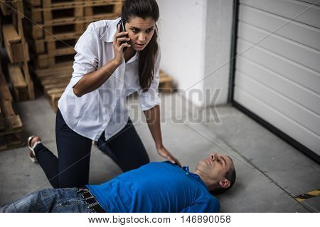 girl calling emergency service for an unconscious man
