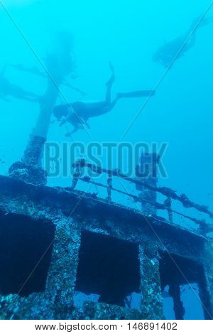 Remaining of cargo ship on ocean bottom and divers Maldives