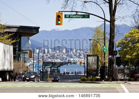 Vancouver, BC - April 20, 2015 - Looking down Burrard St. at the bay and mountains in downtown Vancouver, the heart of the business, shopping and tourist center. The Rockies and West Vancouver can be seen across the bay.