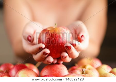 Beautiful Girl Holding An Apple In His Hand. The Girl Offers An Apple.